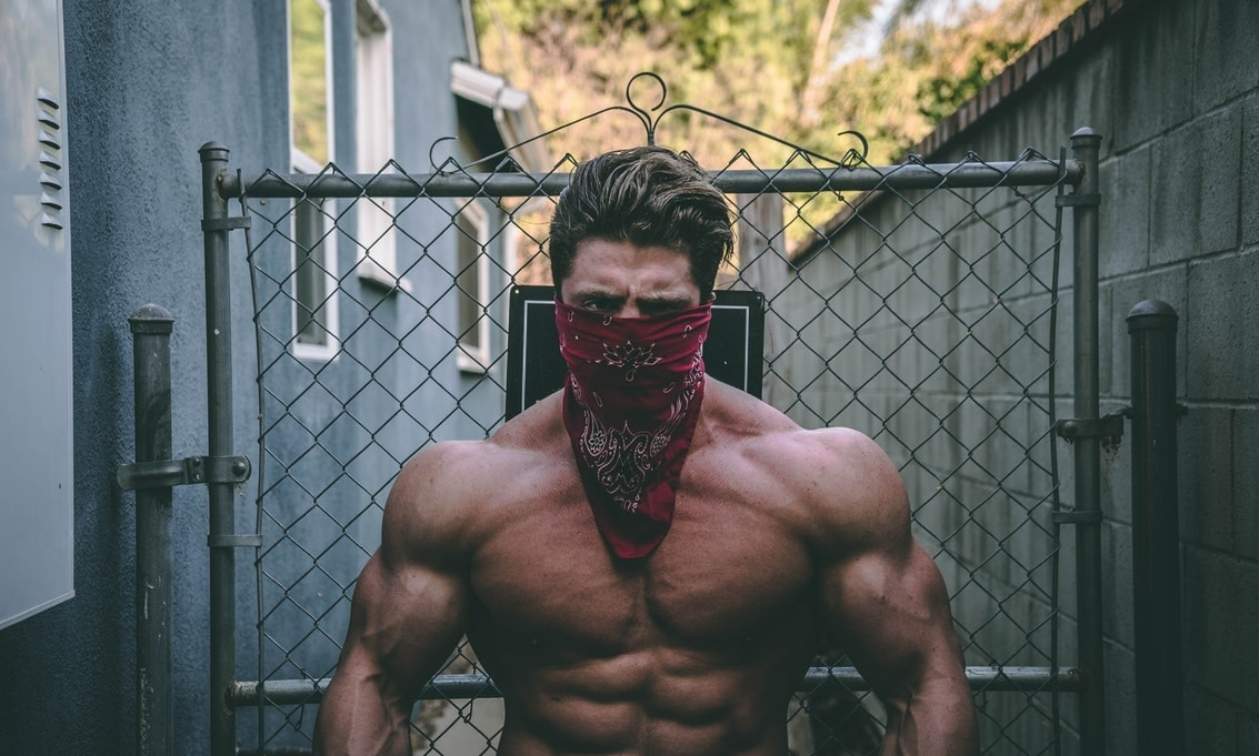 Muscle Bound guy with a handkerchief around mouth showing off shredded and muscular physique