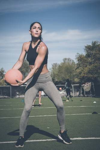 Toned Woman Tossing Medince Ball with a personal trainer in Rochester NY